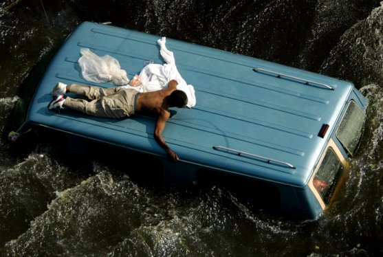 File photo of a man clinging to the top of a vehicle in the aftermath of Hurricane Katrina in New Orleans